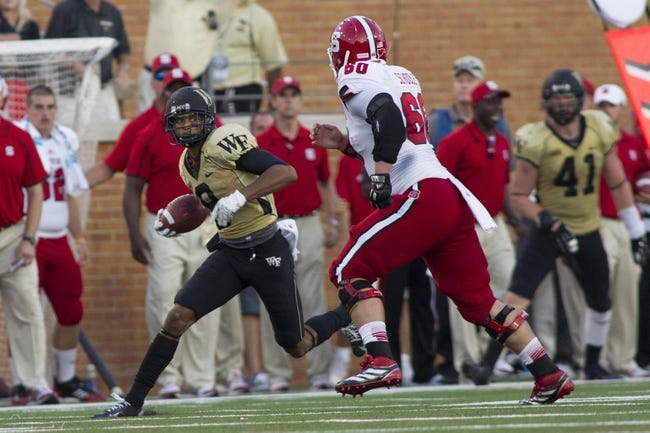 Oct 5, 2013; Winston-Salem, NC, USA; Wake Forest Demon Deacons cornerback Kevin Johnson (9) returns an interception during the fourth quarter against the North Carolina State Wolfpack at BB&T Field. Wake defeated North Carolina State 28-13. Mandatory Credit: Jeremy Brevard-USA TODAY Sports