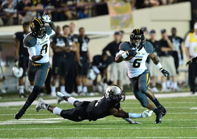 Oct 5, 2013; Nashville, TN, USA; Missouri Tigers running back Marcus Murphy (6) eludes a tackle attempt by Vanderbilt Commodores safety Kenny Ladler (1) during the first half at Vanderbilt Stadium. Mandatory Credit: Don McPeak-USA TODAY Sports