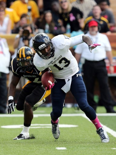 Oct 5, 2013; Hattiesburg, MS, USA; FIU Golden Panthers quarterback E.J. Hilliard (13) is pressured by Southern Miss Golden Eagles defensive back Alex Smith (16) during the second half at M.M. Roberts Stadium. FIU won 24-23. Mandatory Credit: Chuck Cook-USA TODAY Sports