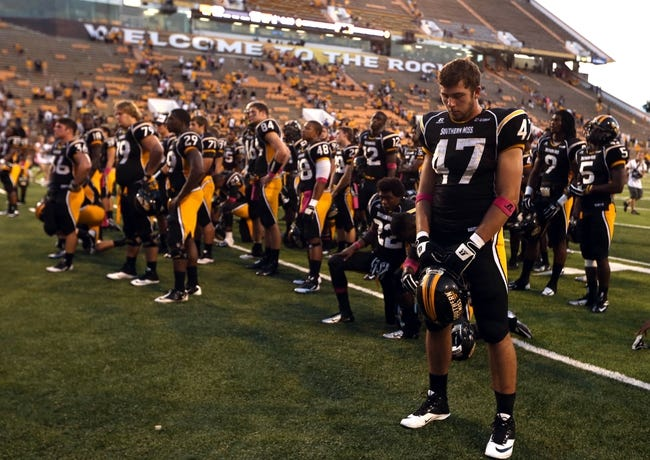 Oct 5, 2013; Hattiesburg, MS, USA; Southern Miss Golden Eagles players, including Nic Bekkers (47) listen as the band plays the school alma mater after their game against the FIU Golden Panthers at M.M. Roberts Stadium. FIU won 24-23. Southern Miss now has a 17-game losing streak dating back to last season. Mandatory Credit: Chuck Cook-USA TODAY Sports