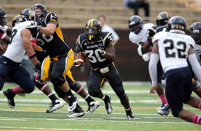 Oct 5, 2013; Hattiesburg, MS, USA; Southern Miss Golden Eagles running back Jalen Richard (30) runs through a hole in the FIU Golden Panthers defense during the second half at M.M. Roberts Stadium. FIU won 24-23. Mandatory Credit: Chuck Cook-USA TODAY Sports