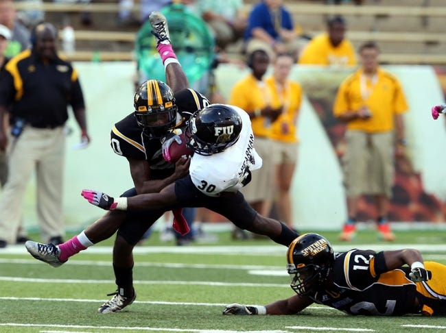 Oct 5, 2013; Hattiesburg, MS, USA; FIU Golden Panthers running back Silas Spearman III (30) is tackled by Southern Miss Golden Eagles defensive back Ed Wilkins (20) during the second half at M.M. Roberts Stadium. FIU won 24-23. Mandatory Credit: Chuck Cook-USA TODAY Sports