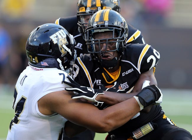 Oct 5, 2013; Hattiesburg, MS, USA; Southern Miss Golden Eagles running back Kendrick Hardy (29) is tackled by FIU Golden Panthers defensive tackle Lars Koht (74) during the second half at M.M. Roberts Stadium. FIU won 24-23. Mandatory Credit: Chuck Cook-USA TODAY Sports
