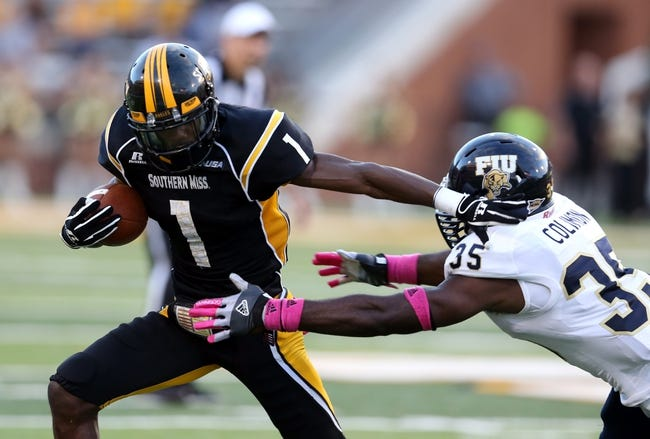 Oct 5, 2013; Hattiesburg, MS, USA; Southern Miss Golden Eagles wide receiver Tyre'oune Holmes (1) tries to get away from the tackle of FIU Golden Panthers linebacker Davison Colimon (35) during the second half at M.M. Roberts Stadium. FIU won 24-23. Mandatory Credit: Chuck Cook-USA TODAY Sports