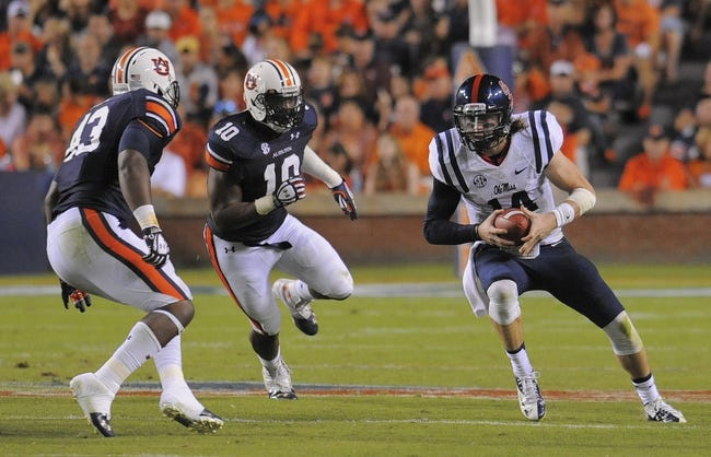 Oct 5, 2013; Auburn, AL, USA; Mississippi Rebels quarterback Bo Wallace (14) tries to evade the Auburn Tigers defense at Jordan Hare Stadium. Mandatory Credit: Shanna Lockwood-USA TODAY Sports