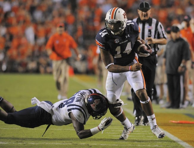 Oct 5, 2013; Auburn, AL, USA; Auburn Tigers quarterback Nick Marshall (14) runs the ball during the third quarter as Mississippi Rebels defensive back Mike Hilton (28) defends  at Jordan Hare Stadium. Mandatory Credit: Shanna Lockwood-USA TODAY Sports