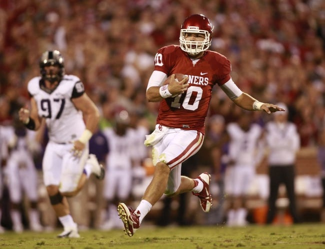 Oct 5, 2013; Norman, OK, USA; Oklahoma Sooners quarterback Blake Bell (10) slides for a first down in the second quarter against the TCU Horned Frogs at Gaylord Family - Oklahoma Memorial Stadium. Mandatory Credit: Tim Heitman-USA TODAY Sports