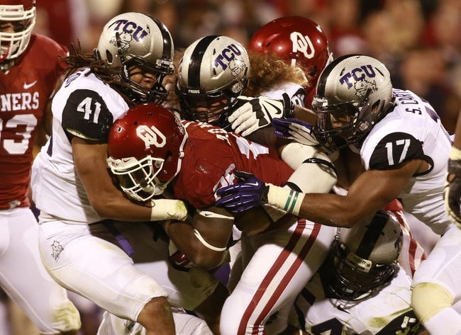 Oct 5, 2013; Norman, OK, USA; Oklahoma Sooners running back Damien Williams (26) is tackled by TCU Horned Frogs linebacker Jonathan Anderson (41) and safety Sam Carter (17) during the fourth quarter of the game at Gaylord Family - Oklahoma Memorial Stadium. The Oklahoma Sooners beat the TCU Horned Frogs 20-17. Mandatory Credit: Tim Heitman-USA TODAY Sports