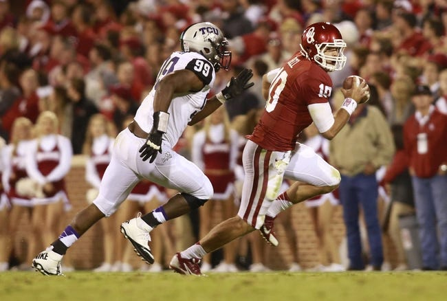 Oct 5, 2013; Norman, OK, USA; Oklahoma Sooners quarterback Blake Bell (10) is chased by TCU Horned Frogs defensive lineman Tevin Lawson (99) during the fourth quarter of the game at Gaylord Family - Oklahoma Memorial Stadium. The Oklahoma Sooners beat the TCU Horned Frogs 20-17. Mandatory Credit: Tim Heitman-USA TODAY Sports