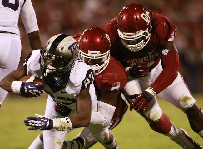 Oct 5, 2013; Norman, OK, USA; TCU Horned Frogs running back B.J. Catalon (23) is tackled by Oklahoma Sooners defensive back Julian Wilson (2) and defensive end Charles Tapper (91) during the fourth quarter at Gaylord Family - Oklahoma Memorial Stadium. The Oklahoma Sooners beat the TCU Horned Frogs 20-17. Mandatory Credit: Tim Heitman-USA TODAY Sports