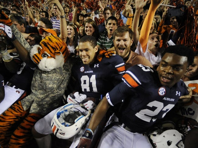 Oct 5, 2013; Auburn, AL, USA; Aubie, Auburn Tigers tight end C.J. Uzomah (81) and running back Johnathan Ford (23) celebrate with fans after the game against the Mississippi Rebels at Jordan Hare Stadium. The Tigers defeated the Rebels 33-20. Mandatory Credit: Shanna Lockwood-USA TODAY Sports