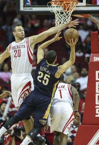 Oct 5, 2013; Houston, TX, USA; New Orleans Pelicans shooting guard Austin Rivers (25) attempts to score during the fourth quarter as Houston Rockets power forward Donatas Motiejunas (20) defends at Toyota Center. The Pelicans defeated the Rockets 116-115. Mandatory Credit: Troy Taormina-USA TODAY Sports