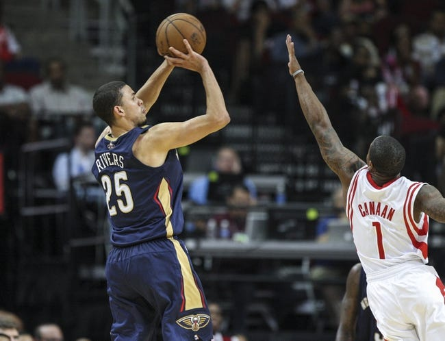 Oct 5, 2013; Houston, TX, USA; New Orleans Pelicans shooting guard Austin Rivers (25) shoots during the fourth quarter as Houston Rockets point guard Isaiah Canaan (1) defends at Toyota Center. The Pelicans defeated the Rockets 116-115. Mandatory Credit: Troy Taormina-USA TODAY Sports