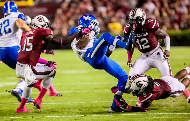 Oct 5, 2013; Columbia, SC, USA; Kentucky Wildcats wide receiver Javess Blue (8) is brought down by South Carolina Gamecocks cornerback Jimmy Legree (15) and South Carolina Gamecocks linebacker Sharrod Golightly (9) in the second half at Williams-Brice Stadium. Mandatory Credit: Jeff Blake-USA TODAY Sports