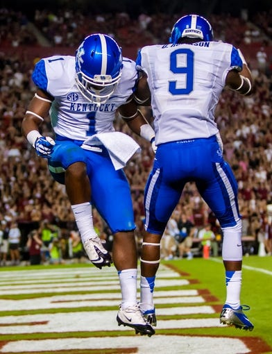 Oct 5, 2013; Columbia, SC, USA; Kentucky Wildcats running back Ryan Timmons (1) and Kentucky Wildcats wide receiver Demarco Robinson (9) celebrate a Timmons touchdown in the fourth quarter at Williams-Brice Stadium. Mandatory Credit: Jeff Blake-USA TODAY Sports