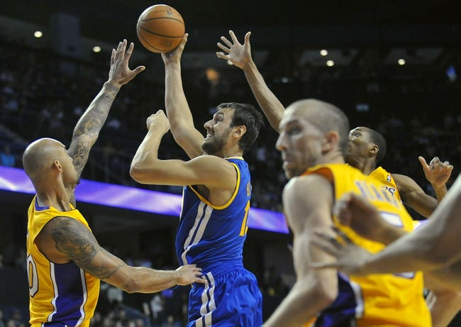 October 5, 2013; Ontario, CA, USA; Golden State Warriors center Andrew Bogut (12) goes in for a basket against the defense of Los Angeles Lakers center Robert Sacre (50) during the first half at Citizens Business Bank Arena. Mandatory Credit: Gary A. Vasquez-USA TODAY Sports