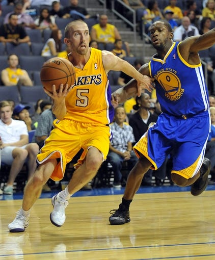 October 5, 2013; Ontario, CA, USA; Los Angeles Lakers point guard Steve Blake (5) moves the ball against the defense of Golden State Warriors point guard Toney Douglas (0) during the second half at Citizens Business Bank Arena. Mandatory Credit: Gary A. Vasquez-USA TODAY Sports