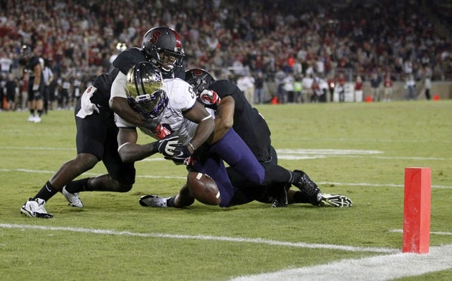 Oct 5, 2013; Stanford, CA, USA; Washington Huskies wide receiver Kevin Smith (8) fumbles the ball before later recovering it after being hit by Stanford Cardinal strong safety Jordan Richards (8) and cornerback Usua Amanam (15) in the fourth quarter at Stanford Stadium. The Cardinal defeated the Huskies 31-28. Mandatory Credit: Cary Edmondson-USA TODAY Sports