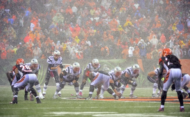 Oct 6, 2013; Cincinnati, OH, USA; New England Patriots quarterback Tom Brady (12) prepares to take a snap in the rain against the Cincinnati Bengals at Paul Brown Stadium. The Bengals won 13-6.  Mandatory Credit: Marc Lebryk-USA TODAY Sports