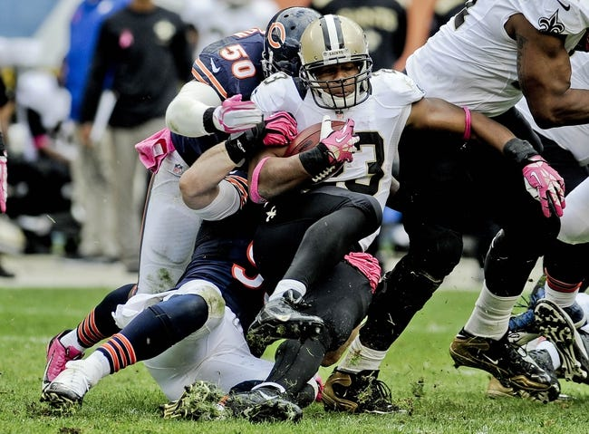 Oct 6, 2013; Chicago, IL, USA; Chicago Bears outside linebacker James Anderson (50) and Chicago Bears defensive end Shea McClellin (99) tackle New Orleans Saints running back Pierre Thomas (23) during the second half at Soldier Field. Mandatory Credit: Matt Marton-USA TODAY Sports