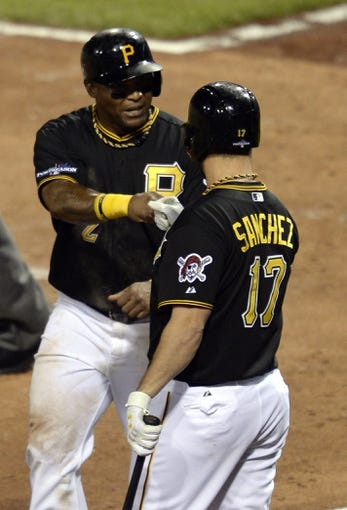 Oct 6, 2013; Pittsburgh, PA, USA; Pittsburgh Pirates right fielder Marlon Byrd (2) is congratulated by teammate Gaby Sanchez (17) after scoring a run against the St. Louis Cardinals during the 8th inning in game three of the National League divisional series playoff baseball game at PNC Park. Mandatory Credit: H.Darr Beiser-USA TODAY Sports