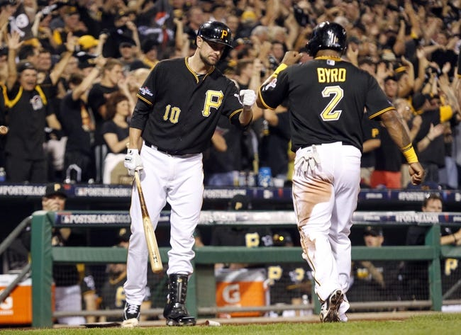 Oct 6, 2013; Pittsburgh, PA, USA; Pittsburgh Pirates right fielder Marlon Byrd (2) is welcomed back to the dugout by Jordy Mercer (10) after scoring a run against the St. Louis Cardinals in the 8th inning in game three of the National League divisional series playoff baseball game at PNC Park. Mandatory Credit: Charles LeClaire-USA TODAY Sports
