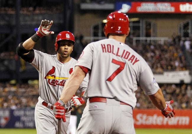Oct 6, 2013; Pittsburgh, PA, USA; St. Louis Cardinals right fielder Carlos Beltran (left) is congratulated by left fielder Matt Holliday (7) after hitting a home run against the Pittsburgh Pirates in the 8th inning in game three of the National League divisional series playoff baseball game at PNC Park. Mandatory Credit: Charles LeClaire-USA TODAY Sports