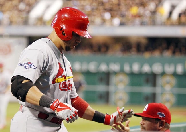 Oct 6, 2013; Pittsburgh, PA, USA; St. Louis Cardinals right fielder Carlos Beltran (left) returns to the dugout after hitting a solo home run against the Pittsburgh Pirates during the eighth inning in game three of the National League divisional series playoff baseball game at PNC Park. Pittsburgh won 5-3. Mandatory Credit: Charles LeClaire-USA TODAY Sports