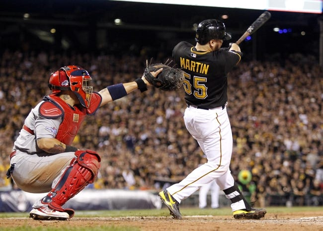 Oct 6, 2013; Pittsburgh, PA, USA; Pittsburgh Pirates catcher Russell Martin (55) hits an RBI single against the St. Louis Cardinals during the eighth inning in game three of the National League divisional series playoff baseball game at PNC Park. Pittsburgh won 5-3. Mandatory Credit: Charles LeClaire-USA TODAY Sports