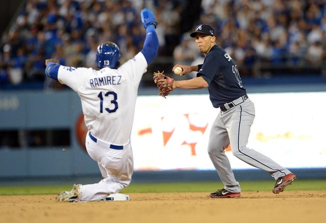 October 6, 2013; Los Angeles, CA, USA; Atlanta Braves shortstop Andrelton Simmons (19) throws to first to turn a double play in the sixth inning as Los Angeles Dodgers shortstop Hanley Ramirez (13) slides into second in game three of the National League divisional series playoff baseball game at Dodger Stadium. Mandatory Credit: Jayne Kamin-Oncea-USA TODAY Sports