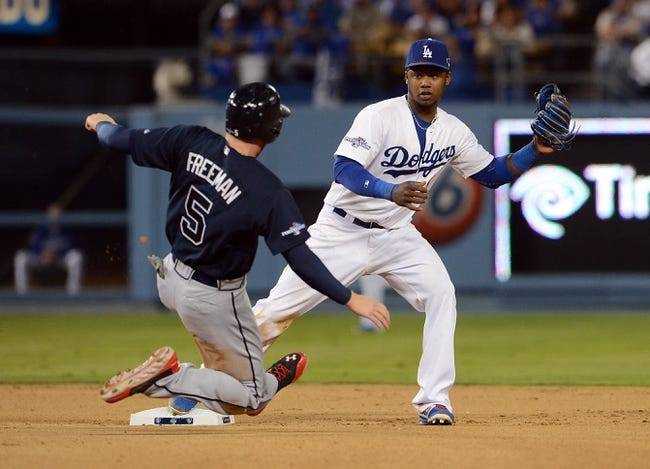 October 6, 2013; Los Angeles, CA, USA; Atlanta Braves first baseman Freddie Freeman (5) is out at second as Los Angeles Dodgers shortstop Hanley Ramirez (13) throws to first to turn a double play in the seventh inning  in game three of the National League divisional series playoff baseball game at Dodger Stadium. Mandatory Credit: Jayne Kamin-Oncea-USA TODAY Sports
