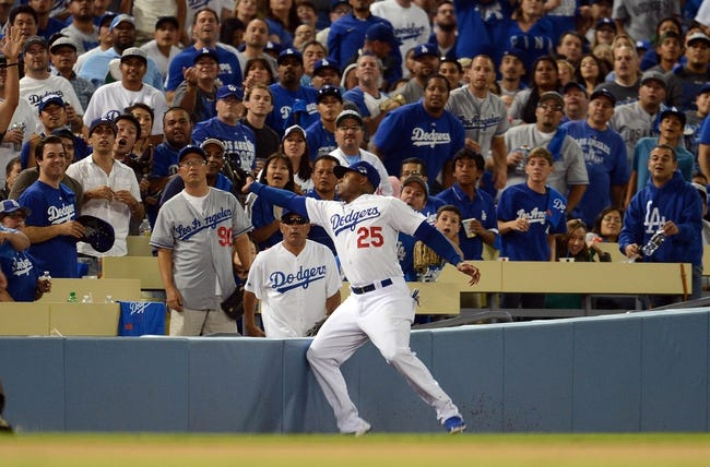 October 6, 2013; Los Angeles, CA, USA; Los Angeles Dodgers left fielder Carl Crawford (25) catches a fly ball in foul territory in the eighth inning against the Atlanta Braves in game three of the National League divisional series playoff baseball game at Dodger Stadium. Mandatory Credit: Jayne Kamin-Oncea-USA TODAY Sports