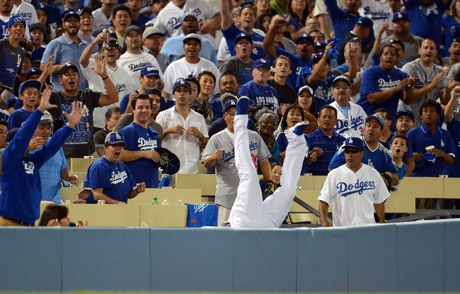 October 6, 2013; Los Angeles, CA, USA; Los Angeles Dodgers left fielder Carl Crawford (25) falls into the stands after he catches a fly ball in foul territory in the eighth inning against the Atlanta Braves in game three of the National League divisional series playoff baseball game at Dodger Stadium. Mandatory Credit: Jayne Kamin-Oncea-USA TODAY Sports
