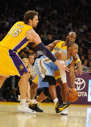 Oct 6, 2013; Los Angeles, CA, USA; Denver Nuggets guard Randy Foye (4) works the ball out of the corner while being defended by Los Angeles Lakers guard Jodie Meeks (20) and forward Pau Gasol (16) during the second half at Staples Center. The Nuggets won 97-88. Mandatory Credit: Christopher Hanewinckel-USA TODAY Sports