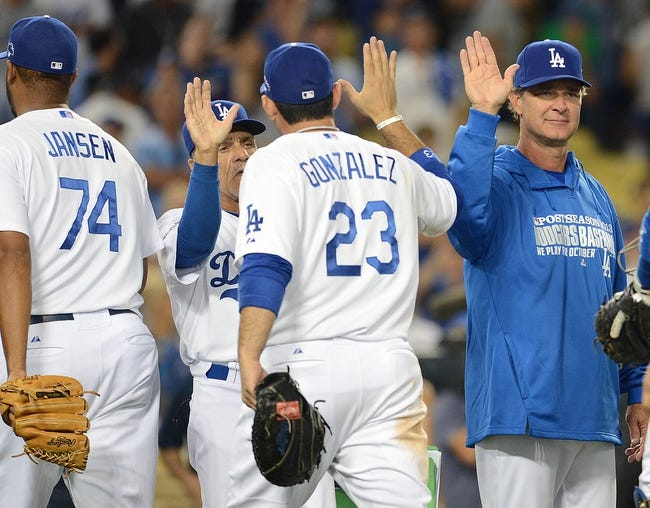 October 6, 2013; Los Angeles, CA, USA; Los Angeles Dodgers manager Don Mattingly (8) celebrates the 13-6 victory against the Atlanta Braves in game three of the National League divisional series playoff baseball game at Dodger Stadium. Mandatory Credit: Jayne Kamin-Oncea-USA TODAY Sports