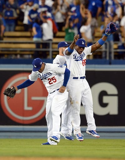 October 6, 2013; Los Angeles, CA, USA; Los Angeles Dodgers left fielder Carl Crawford (25), right fielder Yasiel Puig (66) and outfielder Skip Schumaker (55) celebrate the 13-6 victory against the Atlanta Braves in game three of the National League divisional series playoff baseball game at Dodger Stadium. Mandatory Credit: Jayne Kamin-Oncea-USA TODAY Sports