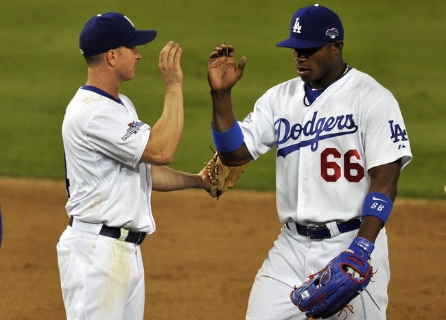 October 6, 2013; Los Angeles, CA, USA; Los Angeles Dodgers right fielder Yasiel Puig (66) celebrates the 13-6 victory with second baseman Mark Ellis (14) against the Atlanta Braves following game three of the National League divisional series playoff baseball game at Dodger Stadium. Mandatory Credit: Robert Hanashiro-USA TODAY Sports