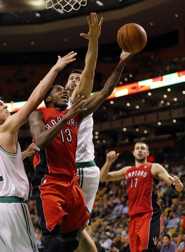 Oct 7, 2013; Boston, MA, USA; Toronto Raptors point guard Dwight Buycks (13) drives the ball past Boston Celtics forward Kelly Olynyk (41) and center Vitor Faverani (38) in the second half at TD Garden. The Raptors defeated the Celtics 97-89. Mandatory Credit: David Butler II-USA TODAY Sports