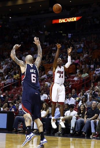 Oct 7, 2013; Miami, FL, USA;  Miami Heat shooting guard Ray Allen (34) takes a three point shot over Atlanta Hawks power forward Pero Antic (6) in the second half at American Airlines Arena. Mandatory Credit: Robert Mayer-USA TODAY Sports