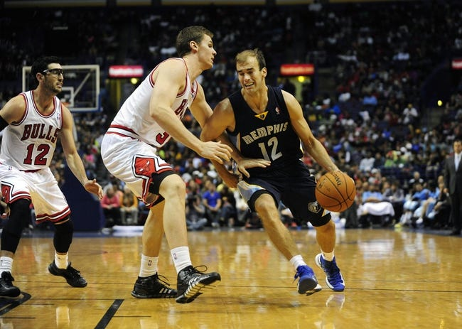 Oct 7, 2013; St. Louis, MO, USA; Memphis Grizzlies forward Nick Calathes (12) handles the ball as Chicago Bulls power forward Erik Murphy (31) defends during the third quarter at Scottrade Center. Chicago defeated Memphis 106-87. Mandatory Credit: Jeff Curry-USA TODAY Sports