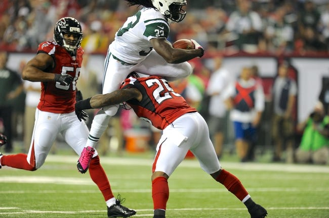 Oct 7, 2013; Atlanta, GA, USA; New York Jets running back Chris Ivory (33) jumps over Atlanta Falcons safety William Moore (25) during the second half at the Georgia Dome. The Jets defeated the Falcons 30-28. Mandatory Credit: Dale Zanine-USA TODAY Sports