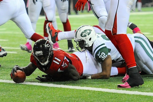 Oct 7, 2013; Atlanta, GA, USA; Atlanta Falcons wide receiver Julio Jones (11) is stopped short of the goal line by New York Jets safety Josh Bush (32) during the first half at the Georgia Dome. The Jets defeated the Falcons 30-28. Mandatory Credit: Dale Zanine-USA TODAY Sports