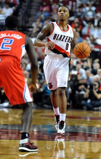 Oct 7, 2013; Portland, OR, USA; Portland Trail Blazers point guard Damian Lillard (0) brings the ball up the court on Los Angeles Clippers point guard Darren Collison (2) during the third quarter of the game at Moda Center. Mandatory Credit: Steve Dykes-USA TODAY Sports