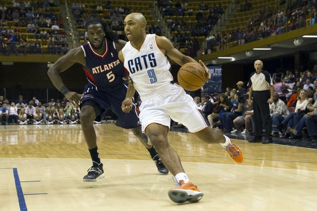 Oct 8, 2013; Asheville, NC, USA; Charlotte Bobcats shooting guard Gerald Henderson (9) drives the ball inside while Atlanta Hawks small forward DeMarre Carroll (5) defends during the first half at the U.S. Cellular Center. Mandatory Credit: Jeremy Brevard-USA TODAY Sports