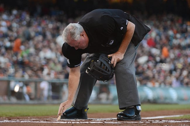 August 19, 2013; San Francisco, CA, USA; MLB umpire Tim Welke (3) cleans home plate during the first inning between the San Francisco Giants and the Boston Red Sox at AT&T Park. The Red Sox defeated the Giants 7-0. Mandatory Credit: Kyle Terada-USA TODAY Sports