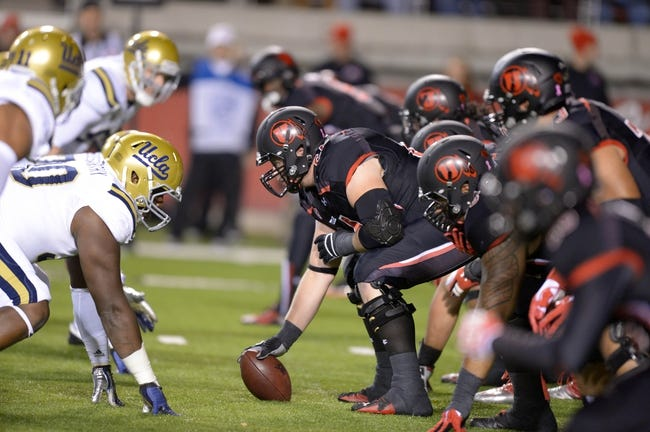 Oct 3, 2013; Salt Lake City, UT, USA; General view of the line of scrimmage as Utah Utes center Vyncent Jones (64) snaps the ball against the UCLA Bruins at Rice-Eccles Stadium. UCLA defeated Utah 34-27. Mandatory Credit: Kirby Lee-USA TODAY Sports