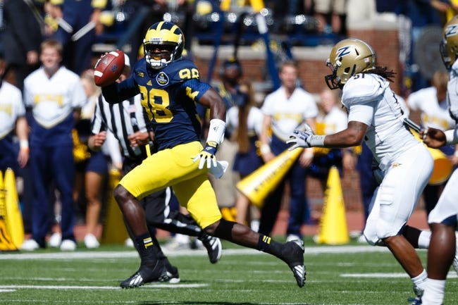 Sep 14, 2013; Ann Arbor, MI, USA; Michigan Wolverines quarterback Devin Gardner (98) rolls out to avaoid Akron Zips linebacker C.J. Mizell (51) at Michigan Stadium. Mandatory Credit: Rick Osentoski-USA TODAY Sports