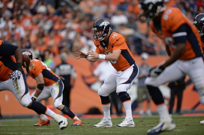 Sep 29, 2013; Denver, CO, USA; Denver Broncos quarterback Peyton Manning (18) prepares to catch a hike of the football against the Philadelphia Eagles in the fourth quarter at Sports Authority Field at Mile High. Mandatory Credit: Ron Chenoy-USA TODAY Sports