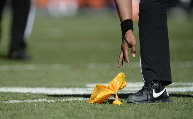 Sep 29, 2013; Denver, CO, USA; General view of a referee picking up a penalty flag during the game between the Philadelphia Eagles against the Denver Broncos at Sports Authority Field at Mile High. Mandatory Credit: Ron Chenoy-USA TODAY Sports