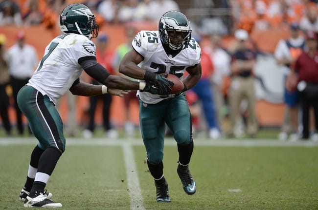 Sep 29, 2013; Denver, CO, USA; Philadelphia Eagles quarterback Michael Vick (7) hands off to running back LeSean McCoy (25) against the Denver Broncos in the fourth quarter at Sports Authority Field at Mile High. Mandatory Credit: Ron Chenoy-USA TODAY Sports